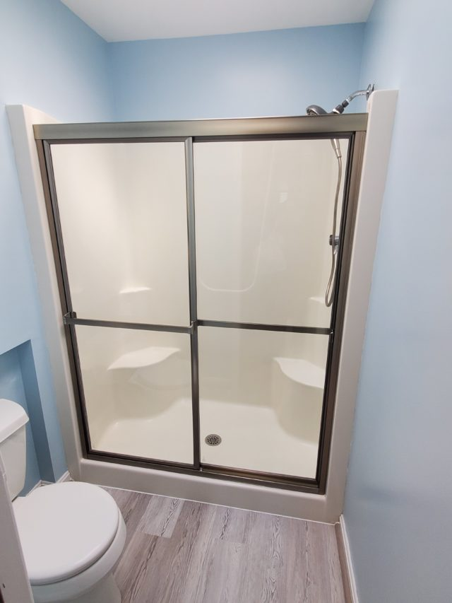 Framed bypass sliding shower doors in fiberglass surrounds.