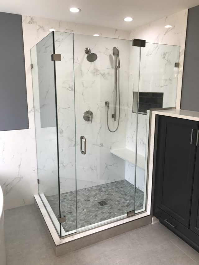 Completely customized glass shower door with custom panel, glass-to-glass pivot hinges, and brushed nickel hardware.