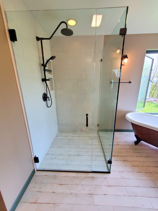Free-standing custom frameless shower door with oil rubbed bronze hardware for wet room bathroom in Martinsburg, West Virginia.