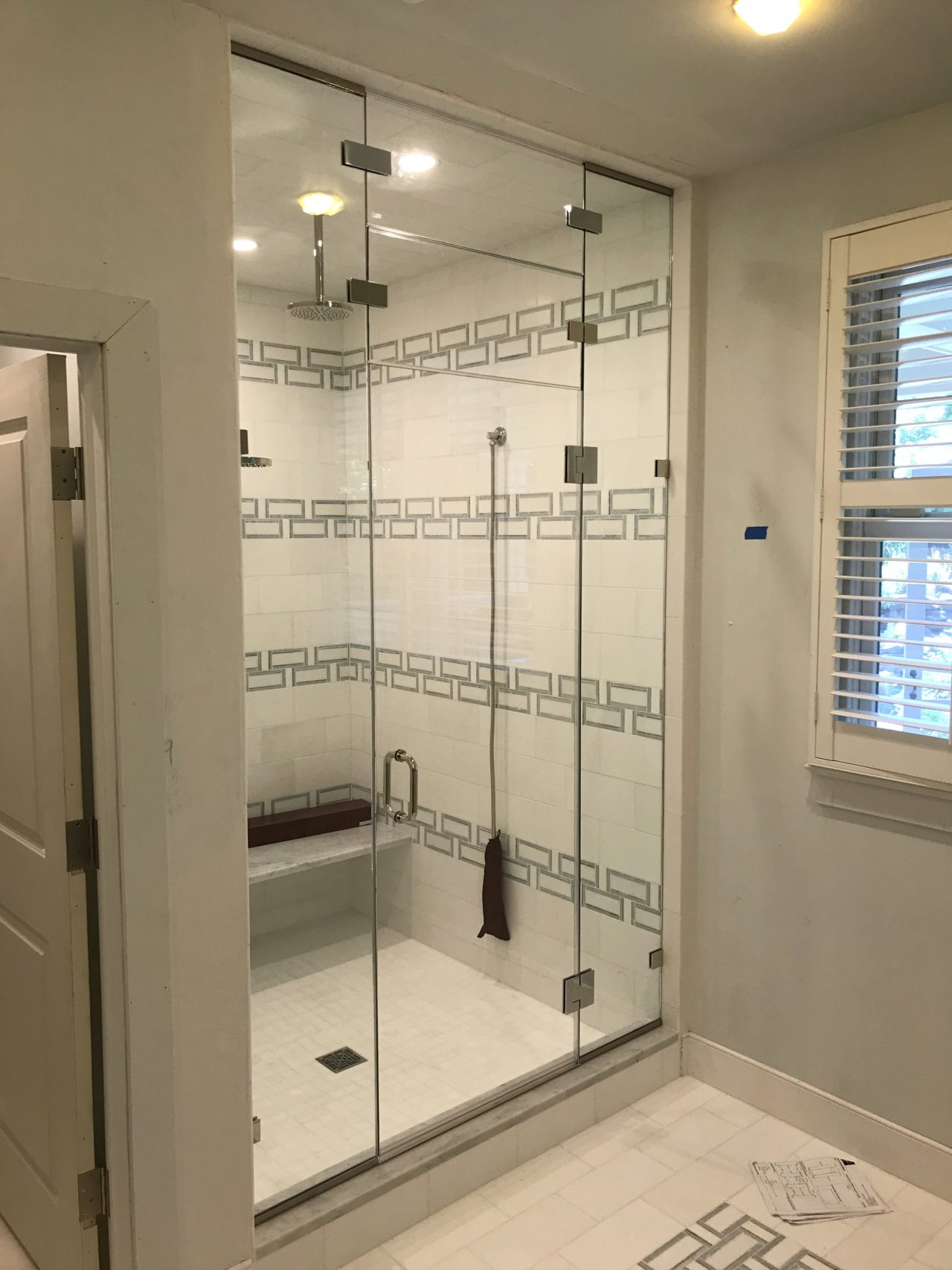 Steam shower unit with fixed and operable transoms.
