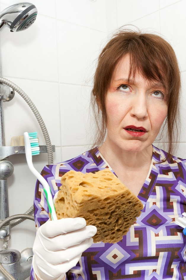 Woman frustrated with cleaning shower door glass in bathroom